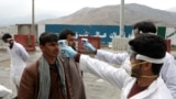 Afghan health workers check the temperature of travelers arriving in the capital Kabul on March 24