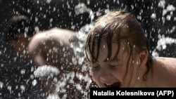 A girl cools off in a fountain amid soaring temperatures in Moscow. (AFP/Natalia Kolesnikova)