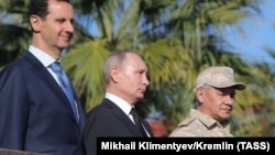 Syrian President Bashar al-Assad (left), Russian President Vladimir Putin (center), and Russian Defense Minister Sergei Shoigu visit the Hmeimim military base in Latakia Province on December 11.