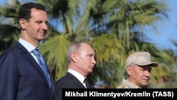 Сирия президенті Башар Асад (сол жақта), Ресей президенті Владимир Путин (ортада) және Ресей қорғаныс министрі Сергей Шойгу. Хмеймим әуе базасы, Сирия. 11 желтоқсан 2017 жыл.