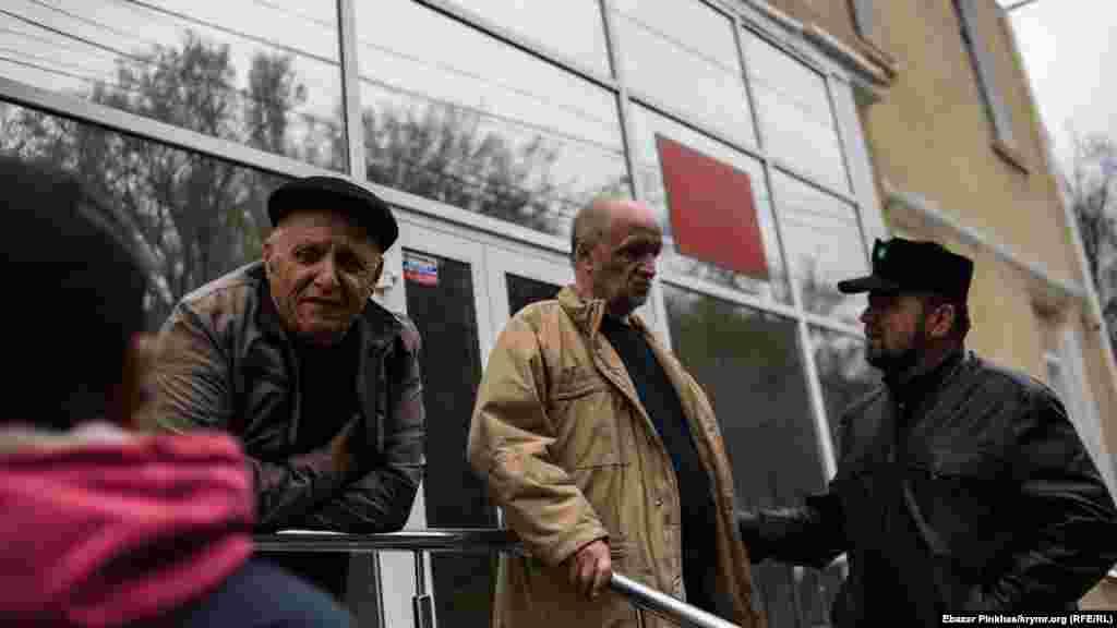 Bekir Degermenci ve Asan Çapuh mahkeme bosağasındaolarğa qol tutmaq içün kelgen adamlarnen ükümden soñ qonuşa