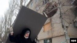 Жінка несе будівельний матеріал після обсрілів у Авдіївці, 3 лютого 2017 року