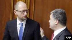 Ukrainian President Petro Poroshenko (right) speaks to Prime Minister Arseniy Yatsenyuk after a parliamentary session in Kyiv on July 31.