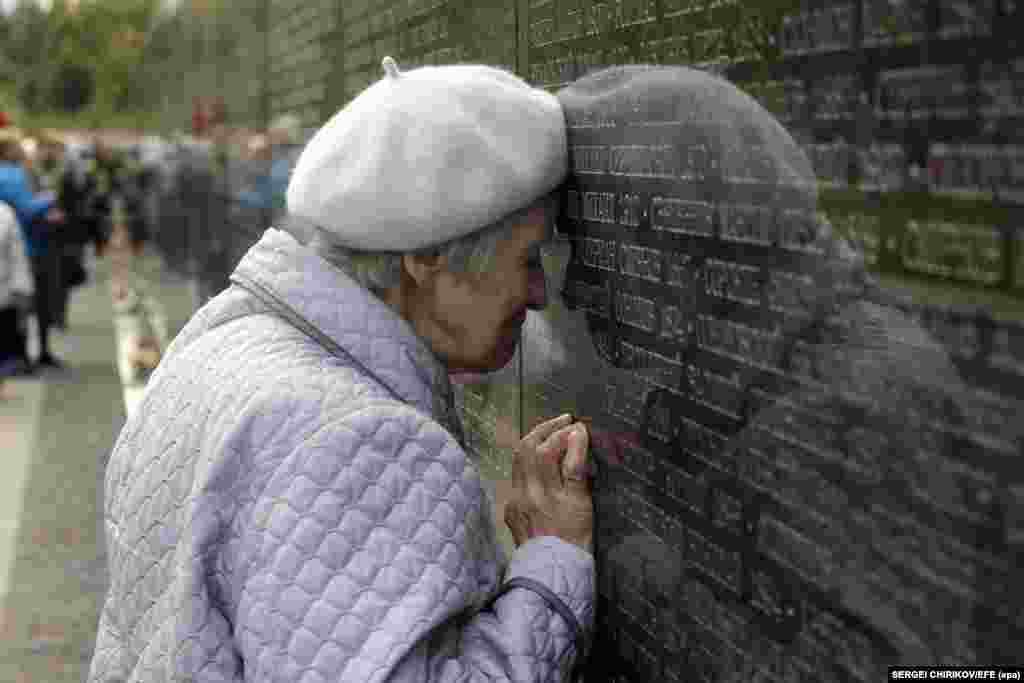 An elderly Russian woman, a granddaughter of a Stalin terror victim, touches her head to the name of her grandfather that is engraved on a memorial wall outside Moscow. The Memory Garden memorial was unveiled and blessed on September 27 in memory of 20,762 people executed at the site during Stalin's political terror from 1937-38. (epa-efe/Sergei Chirikov)