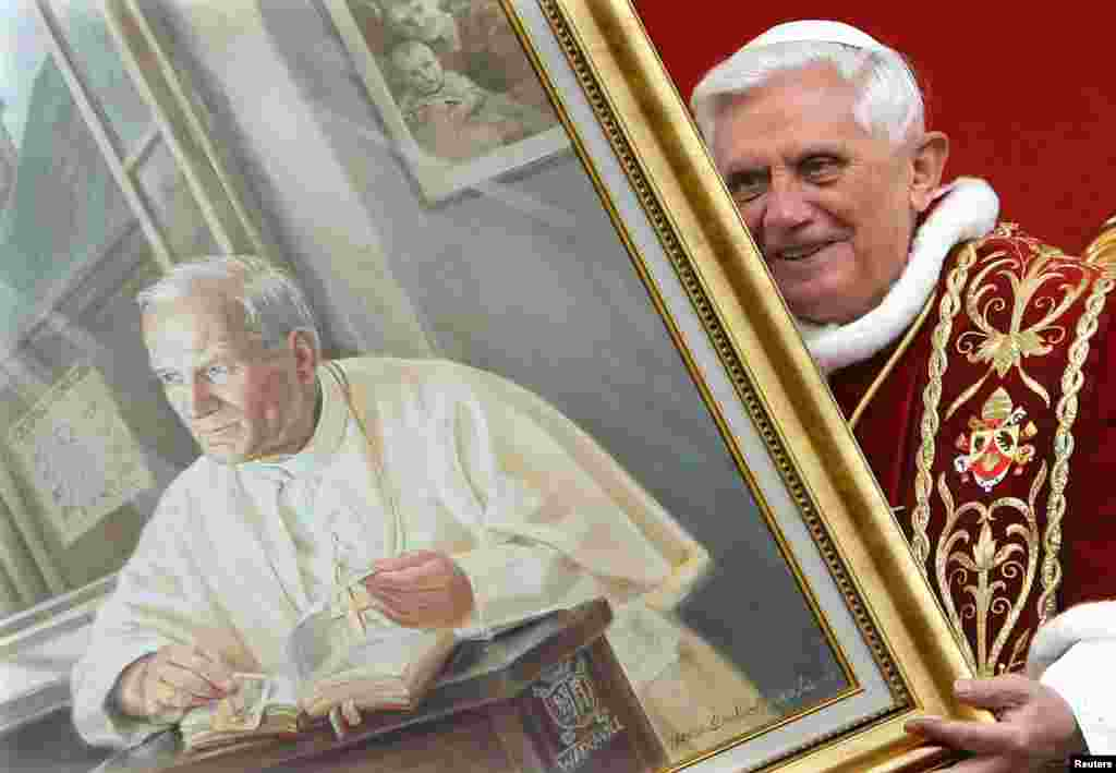 Pope Benedict holds a portrait of the late Pope John Paul II during a meeting with the faithful at Wadowice, Poland, in May 2006. John Paul moved a major step closer to Roman Catholic sainthood in January 2011 when Benedict approved a decree attributing a miracle to him and announced his beatification, a step from sainthood.