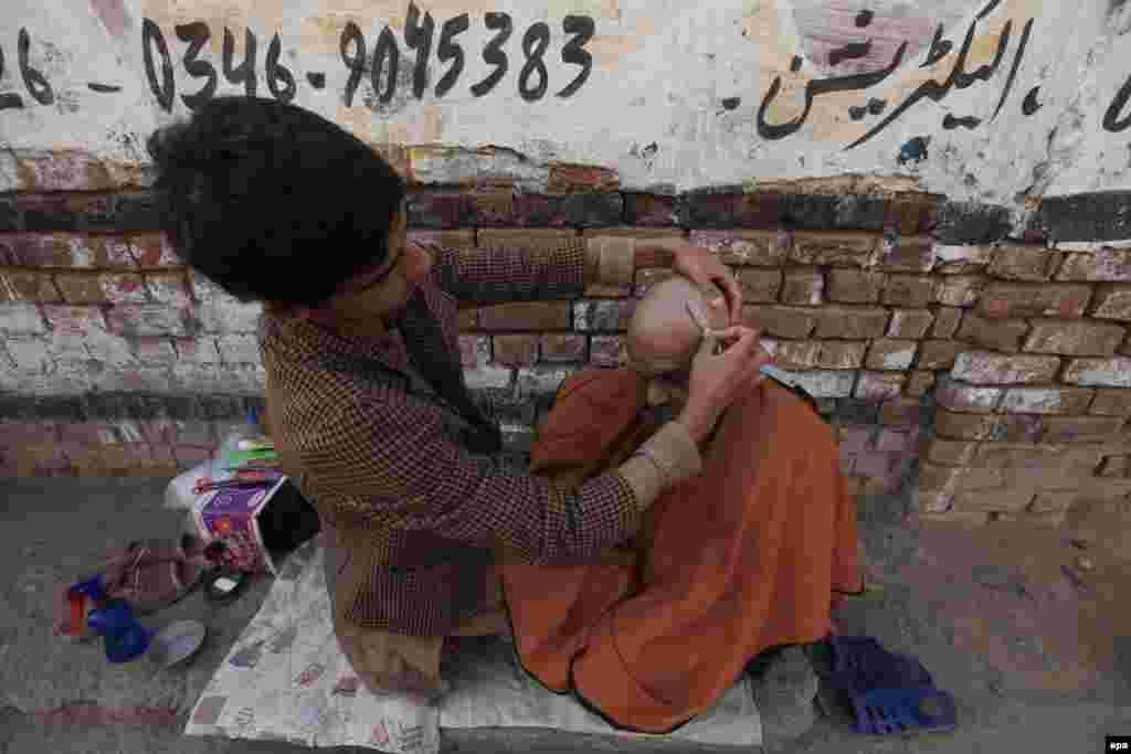 A Pakistani barber shaves a customer's head at a roadside shop in Peshawar. (epa/Bilawal Arbab)