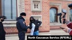 Полицейский спрашивает документы у участника акции у посольства Франции в Москве, 29 октября 2020