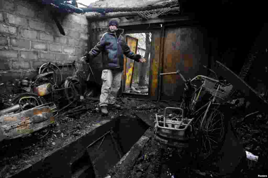 A local resident gestures while standing in his garage, which was damaged during the recent exchange of fire between Ukrainian government forces and Russia-backed separatists, on the outskirts of Donetsk, Ukraine. (Reuters/Alexander Ermochenko)