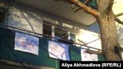 Зейнеткер Зоя Юртаева пәтерінің балконында наразылық акциясын өткізіп тұр. Қарабұлақ кенті, Алматы облысы, 18 желтоқсан 2015 жыл.