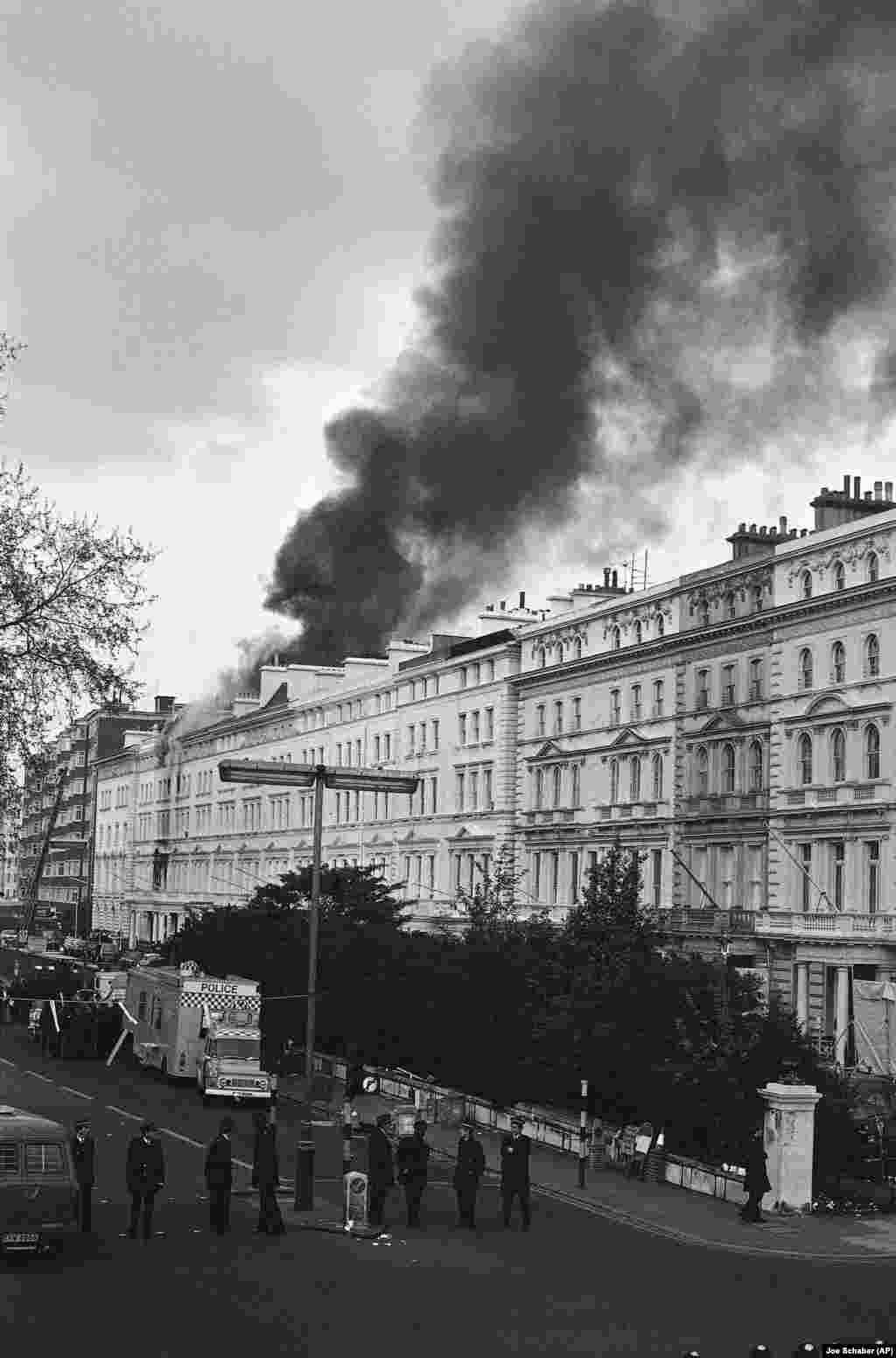 Black smoke pours from the roof of the embassy on May 5, after police and an SAS unit ended the six-day siege. Machine-gun fire was heard and an explosion followed.