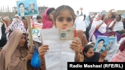 FILE: Thousands of women, children, and men held up photos, placards, or the national ID cards of their missing family members in Peshawar, Pakistan in April 2018.