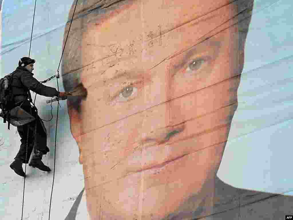 Працівник очищає величезний плакат кандидата в президенти Віктора Януковича в Києві 7 лютого Янукович, голова Партії регіонів, змагається в останньому турі президентських виборів з прем'єр-міністром Юлією ТимошенкоPhoto by Volodymyr Strumkovsky for AFP Фото Володимира Strumkovsky для AFP