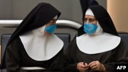 Two nuns wait at Mexico City's international airport wearing surgical masks to ward off the flu.