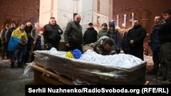 Mourners pay their respects to a fallen combatant affiliated with the nationalist Right Sector group who was buried in Kyiv on January 18.