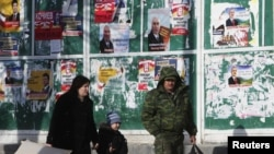 People pass by campaign posters in Tskhinvali displaying presidential candidates in South Ossetia's March 25 repeat election.
