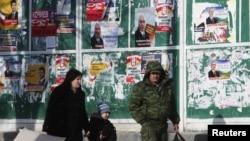 Люди проходят мимо агитационных материалов кандидатов в президенты Южной Осетии