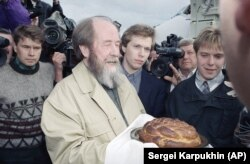Solzhenitsyn receives a traditional Slavic greeting of bread and salt upon his arrival in Vladivostok after returning to Russia following an absence of two decades.