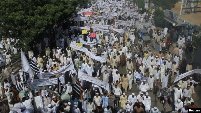 Pakistani protesters hold banners and flags while taking part in an anti-American protest rally in Karachi on September 21.