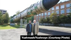 Stanislav Yus (right) stands with Christopher Miller outside Ukraine's Yuzhmash rocket factory.