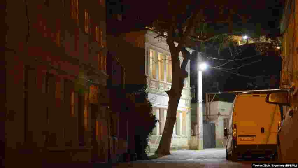 Старый дом причудливо подсвечен фонарем