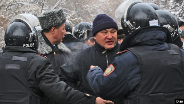 Kazakh police try to pacify protesters in Almaty who were rallying against measures taken by the authorities to suppress demonstrations in the oil town of Zhanaozen. At least 16 people were killed in violent clashes between police and demonstrators.
