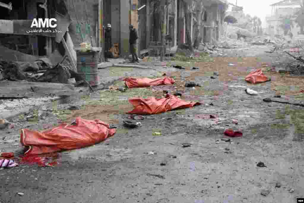 Dead bodies in body bags lie on the ground after a bombing in the Jibb al-Quebeh neighborhood of Aleppo, Syria. At least 45 people fleeing violence were reported killed in the shelling of the rebel-held neighborhood. (epa/Aleppo Media Center)