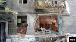 Чоловік розбирає завали у кімнаті після обстрілу будинку, Горлівка, 27 лтпня 2014