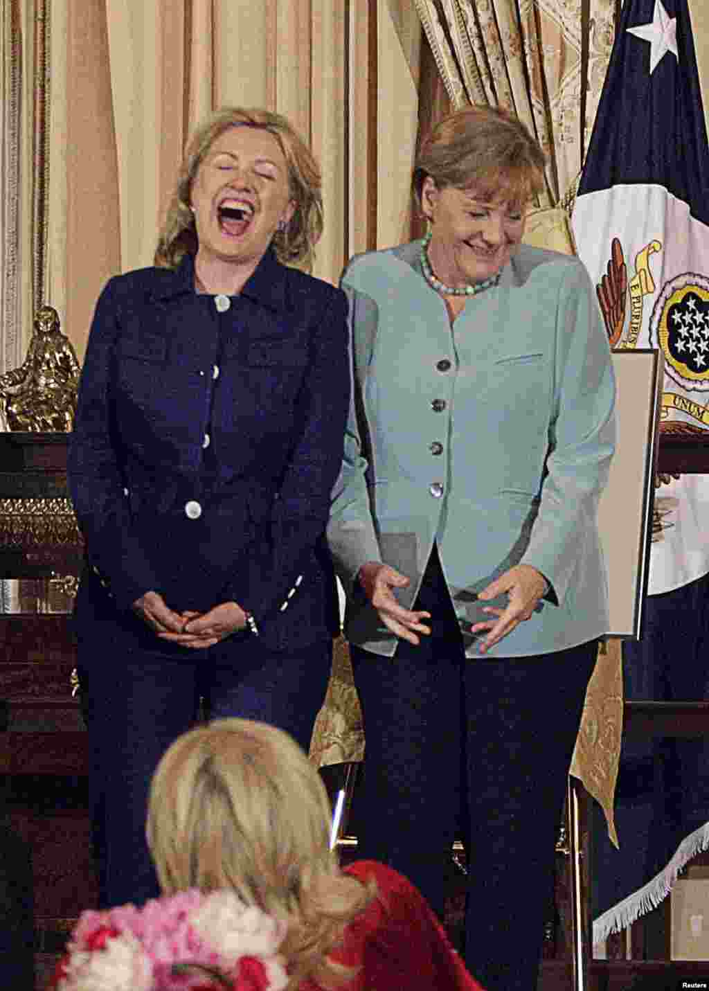 Clinton laughs with German Chancellor Angela Merkel during a luncheon held in Merkel's honor at the State Department on June 7, 2011.