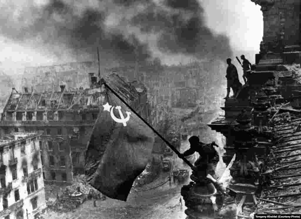 Soviet flag flies above the Reichstag building as Berlin smolders, May 2, 1945