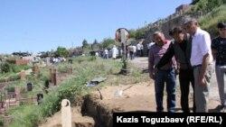 Болат Калдыбаев (в середине) у могилы 49-летнего сына Таира Калдыбаева, найденного 5 июля повешенным в СИЗО. Алматы, 8 июля 2016 года.