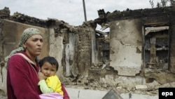 An ethnic Uzbek woman on June 16 carries her child past homes destroyed during the clashes in her village, Kyr-Aryk in the Osh region.