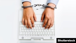 Generic -- Female hands in handcuffs with laptop. Internet censorship. (©Shutterstock)