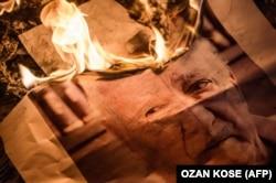 На демонстрации в Стамбуле жгут постер с портретом Фетхуллаха Гюлена. 18 июля 2016 года.