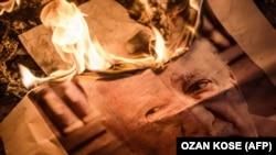 Etirazçılar Fethullah Gülen-in şəklini yandırırlar.