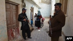 Pakistani police escort a team of polio health workers during a polio vaccination campaign in Quetta on February 15.