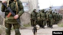 Вооруженные люди в военной форме без опознавательных знаков близ Симферополя. 14 марта 2014 года. После аннексии Крыма Москвой президент России Владимир Путин признал, что в Крыму действовали российские военные.