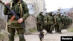 Ukraine -- Armed men, believed to be Russian servicemen, walk outside a Ukrainian military base in Perevalnoye, near the Crimean city of Simferopol, March 14, 2014.