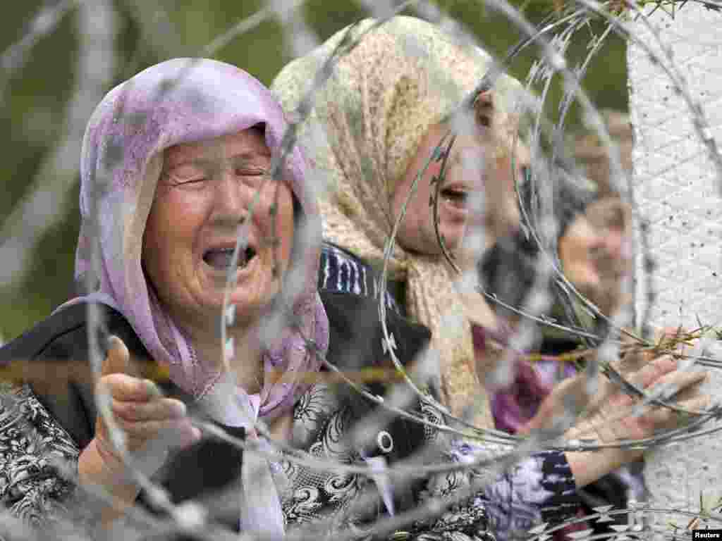 Ethnic Uzbek refugees cry as they gather on the Kyrgyz-Uzbek border and await permission to enter Uzbekistan. Photo by Shamil Zhumatov for Reuters