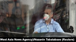 A bus driver wearing a protective mask to prevent contracting coronavirus, as he drives the bus in Tehran, Iran February 25, 2020.