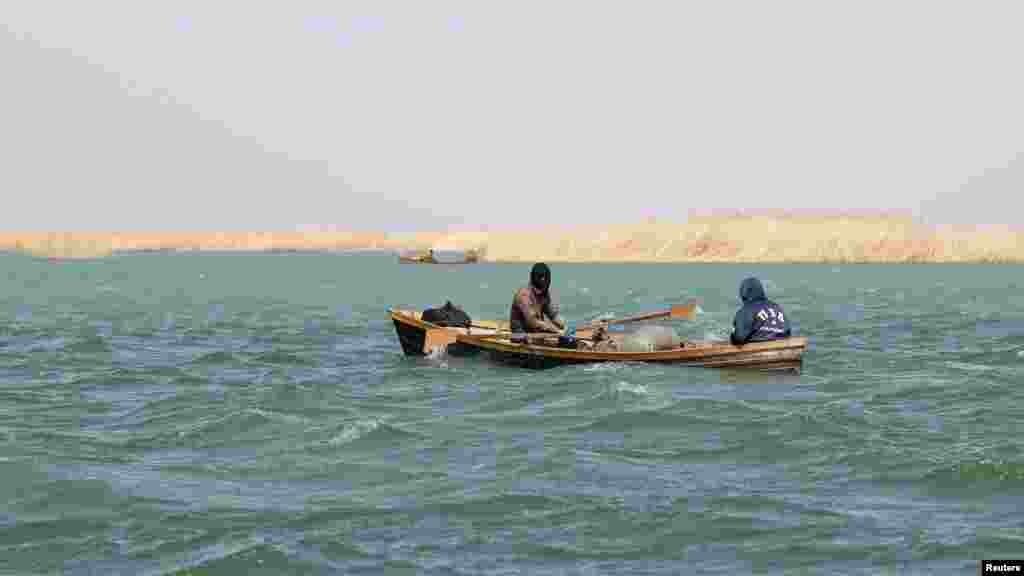 Рыбаки сидят в лодке близ села Каратерен.