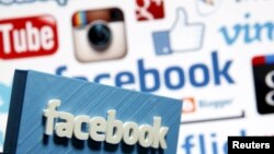 Facebook желісі логотипі басқа компаниялардың белгілерінің арасында тұр. (Көрнекі сурет)