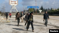 Rebel fighters walk in December around the Al-Hamidiyeh base, one of two military posts they took control of from government forces in the northwestern province of Idlib.