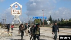 Rebel fighters walk around al-Hamidiyeh base, one of two military posts they took control of from government forces in the northwestern province of Idlib, in December.