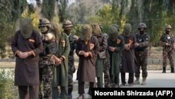 FILE: Officials of Afghanistan's National Directorate Security (NDS) intelligence agency escort alleged Taliban fighters after they are presented to media in Jalalabad in January.