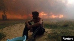 Russia - A man sits on the ground while a house burns due to severe heat, outside the town of Vyksa, 29Jul2010