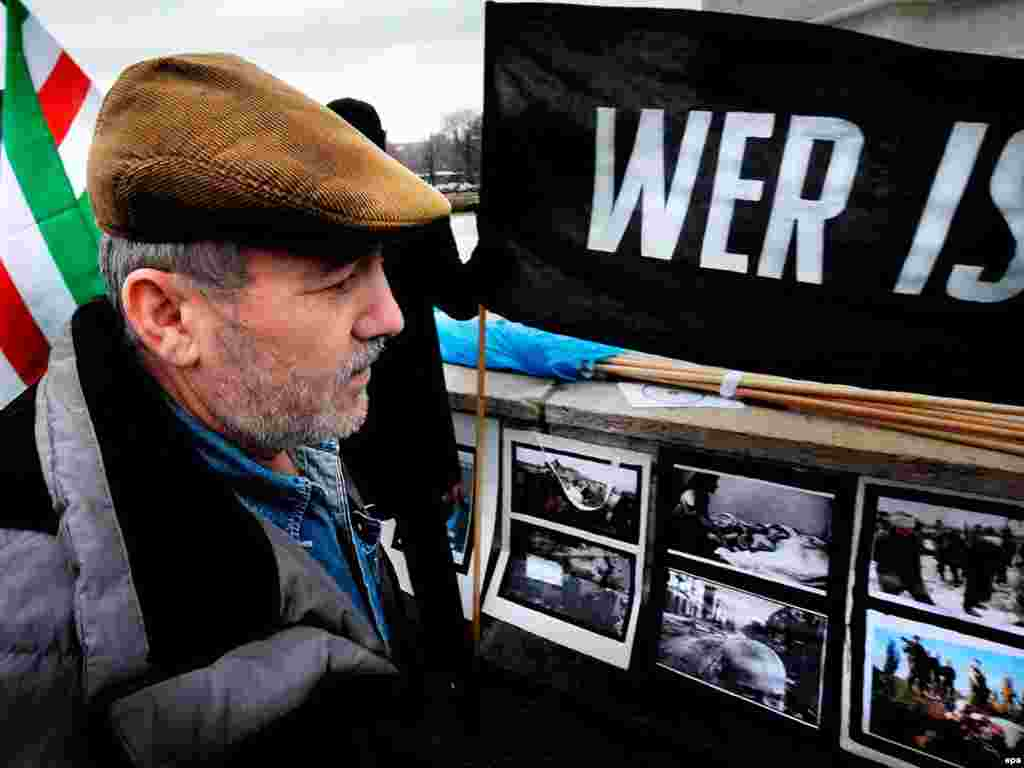 Austria -- Ali Israilov [father of Umar] - epa01609082 Ali Israilov stands looks at pictures and a banner saying 'Who's next' during a manifestation in memory of Chechen Umar Israilov, a former Chechen rebel and bodyguard to Chechen President Ramzan Kadyrov who was shot dead in Vienna on 20 January in Vienna, Austria, 22 January 2009. Umar Israilov came public with allegations of torture. EPA/Rene Van Bakel
