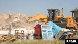 """Сот """"заңсыз салынған"""" деп шешім шығарған үйді бұзып жатқан трактор. Бақай ауылы, Алматы, 7 шілде 2006 жыл."""