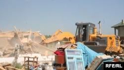 Бульдозер разрушает дома в поселке Бакай близ Алматы. 7 июля 2009 года.