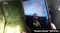Saodat Solehova holds up a cellphone picture of her son, Nekqadam Solehov, a prison inmate who Tajik authorities said died of food poisoning.
