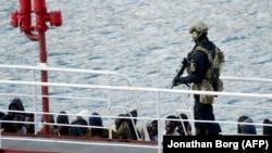 Мальтийский полицейский охраняет арестованных мигрантов в порту Валетты. 28 марта 2019 года